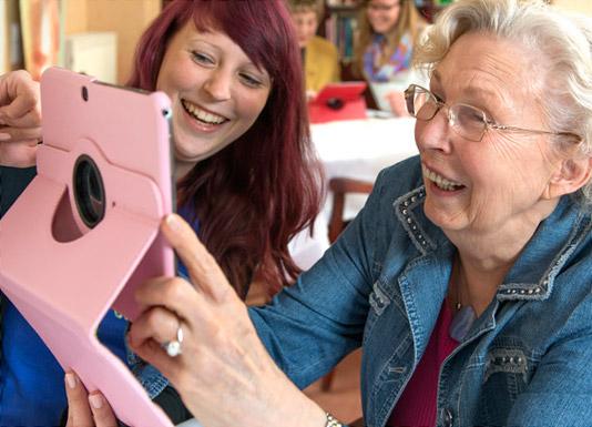 Eine junge Frau erklärt einer alten Frau wie ein Tablet-Computer funktioniert.
